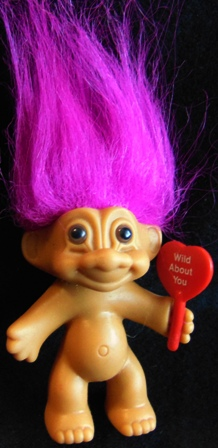 troll dolls holding flags and signs with messages on them